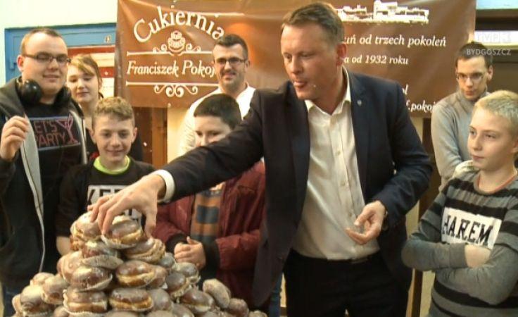 Radny Jakubaszek zjada pączki z dziećmi, po przegranym zakładzie