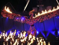 Feniks przelatujący nad tlącym się ogniem olimpijskim (fot. PAP/EPA)