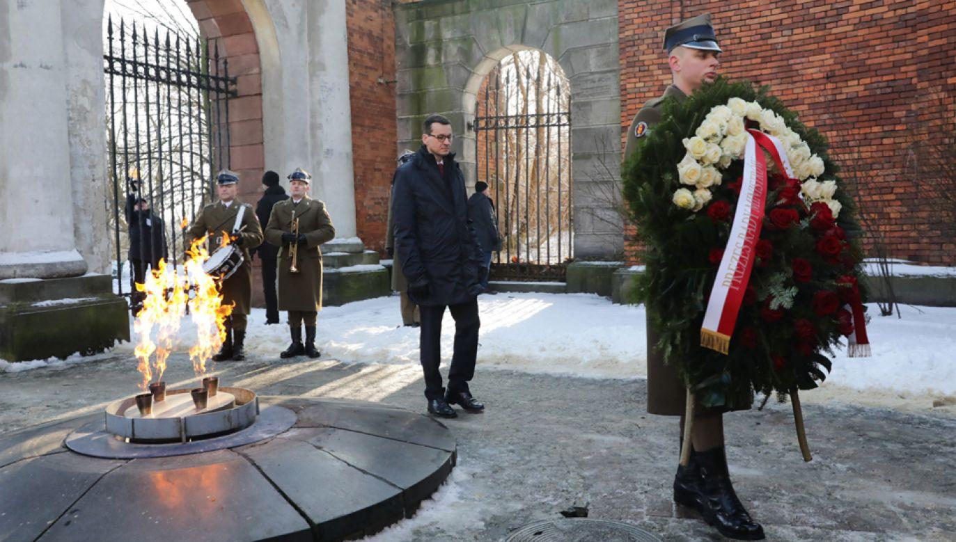 Premier Mateusz Morawiecki (C) podczas uroczystości składania wieńców przed Bramą Straceń (fot. PAP/Tomasz Gzell)