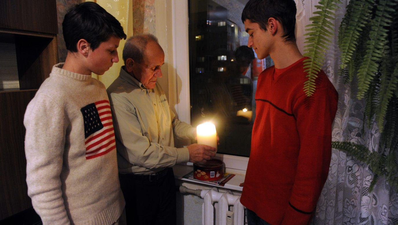 Działacz solidarnościowy Zygmunt Woźniak z wnukami Przemkiem i Wojtkiem w 31 rocznicę stanu wojennego zapalił i postawił w oknie symboliczną świecę (fot. arch. PAP/ Marcin Bielecki)