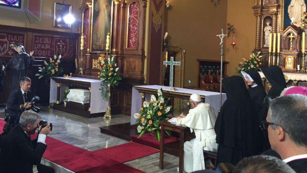 Papież wpisuje się do księgi pamiątkowej (fot. Episkopat)