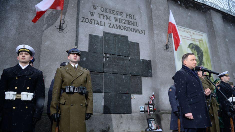 Prezydent Andrzej Duda składa kwiaty przed tablicą upamiętniającą torturowanych i zamęczonych więźniów politycznych w czasie terroru komunistycznego - przy ul. Rakowieckiej/PAP/Jacek Turczyk
