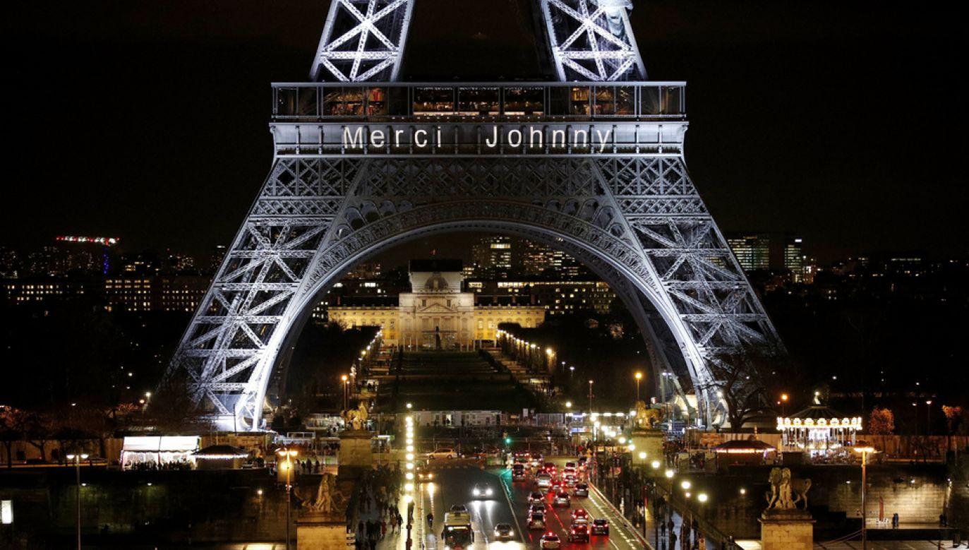 """Przez cały weekend wieża Eiffla jarzyć się będzie światełkami ułożonymi w napis """"Merci Johnny"""" (fot. EPA/YOAN VALAT)"""