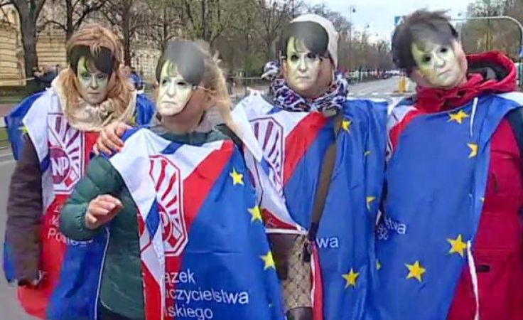Uczestnicy protestu ukryci za okazjonalnymi maskami z podobizną  Joanny Kluzik-Rostkowskiej.