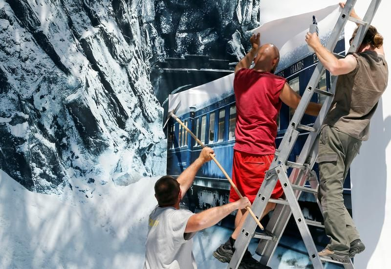 Technicy zawieszają plakaty zakwalifikowanych filmów (fot. REUTERS/Regis Duvignau)