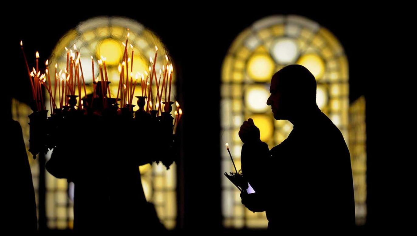 Prawosławny zapala świecę podczas mszy w Wielki Piątek w cerkwi w Sofii (fot. arch. PAP/VASSIL DONEV)
