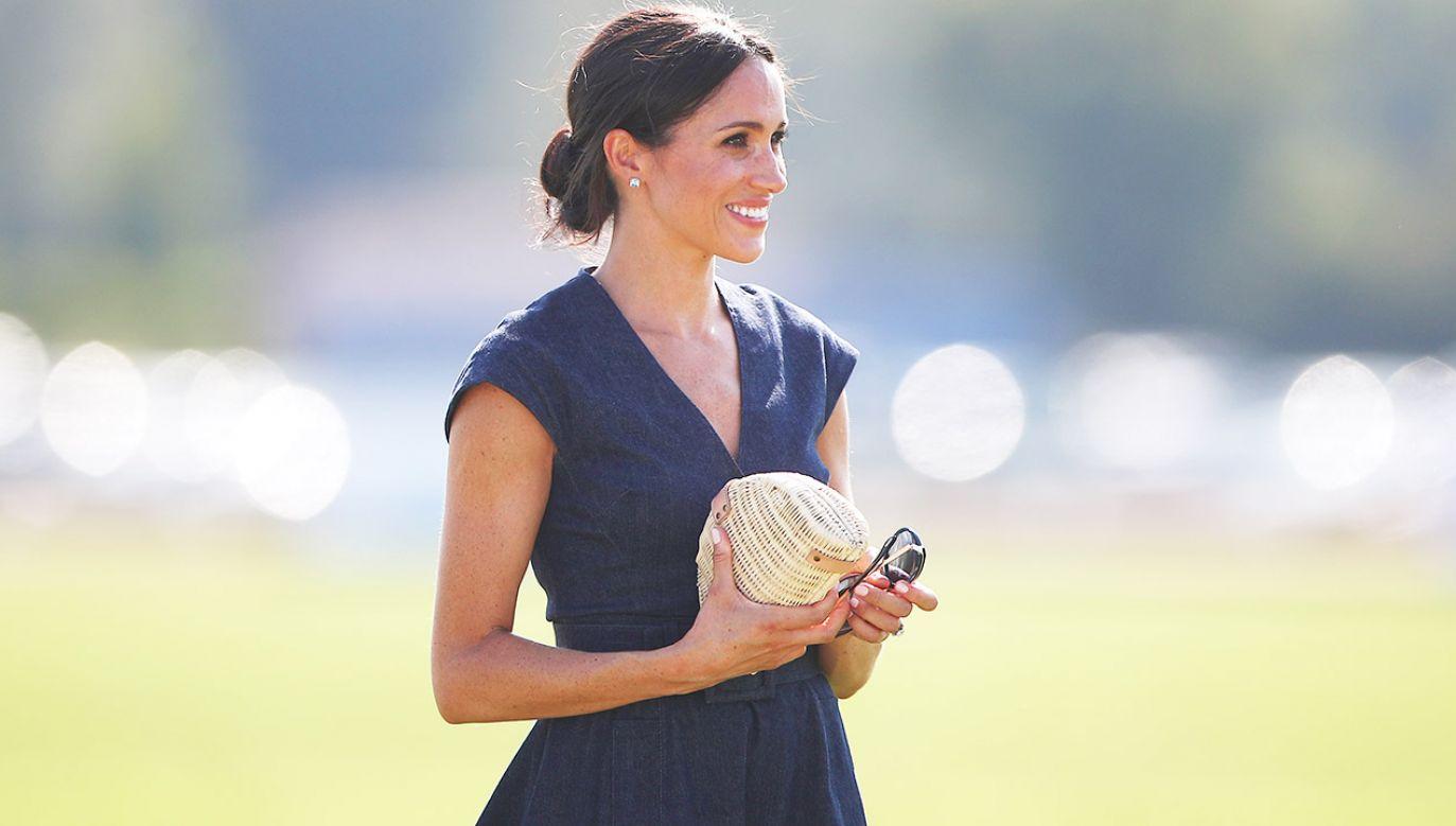 Decydując się na letnią sukienkę z ciemnego denimu Meghan zerwała z nieoficjalną królewską tradycją (fot.  REUTERS/Hannah McKay)