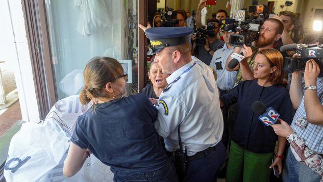 Protestujący w Sejmie rodzice dzieci niepełnosprawnych próbują wywiesić transparent po angielsku informujący o prowadzonym przez nich proteście. Interweniuje Straż Marszałkowska (fot.  PAP/Jakub Kamiński)