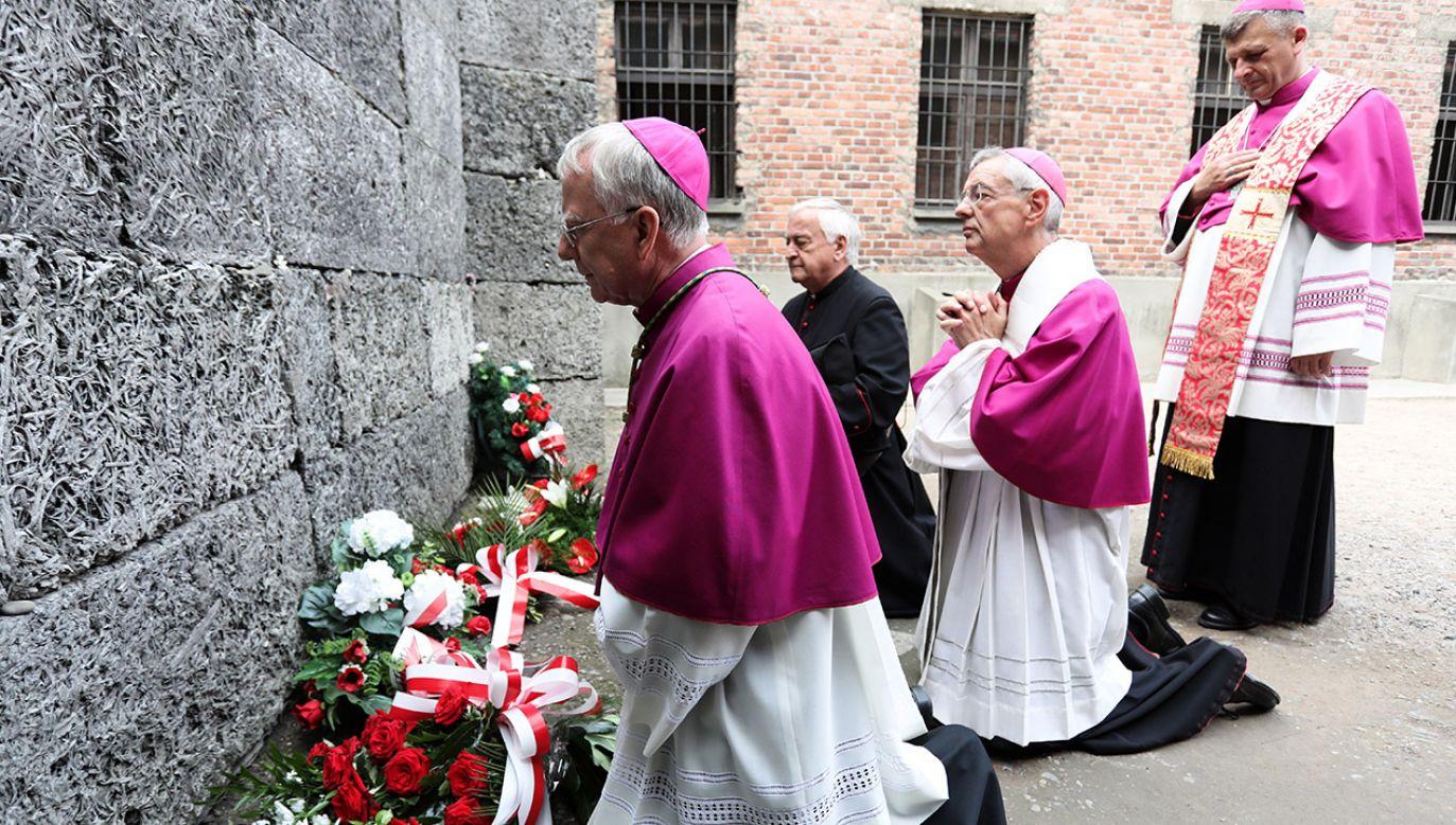 Abp Marek Jędraszewski (L) podczas uroczystości 77. rocznicy śmierci ojca Maksymiliana Kolbego, 14 bm. przed Ścianą Straceń na terenie byłego niemieckiego nazistowskiego obozu zagłady Auschwitz (fot. PAP/Jan Graczyński)