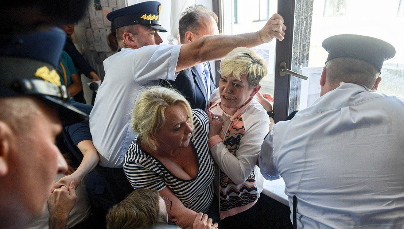 Protestujący w Sejmie rodzice dzieci niepełnosprawnych próbowali wywiesić za oknem budynku transparent informujący o prowadzonym przez nich proteście - interweniuje straż marszałkowska (fot.  PAP/Jakub Kamiński)