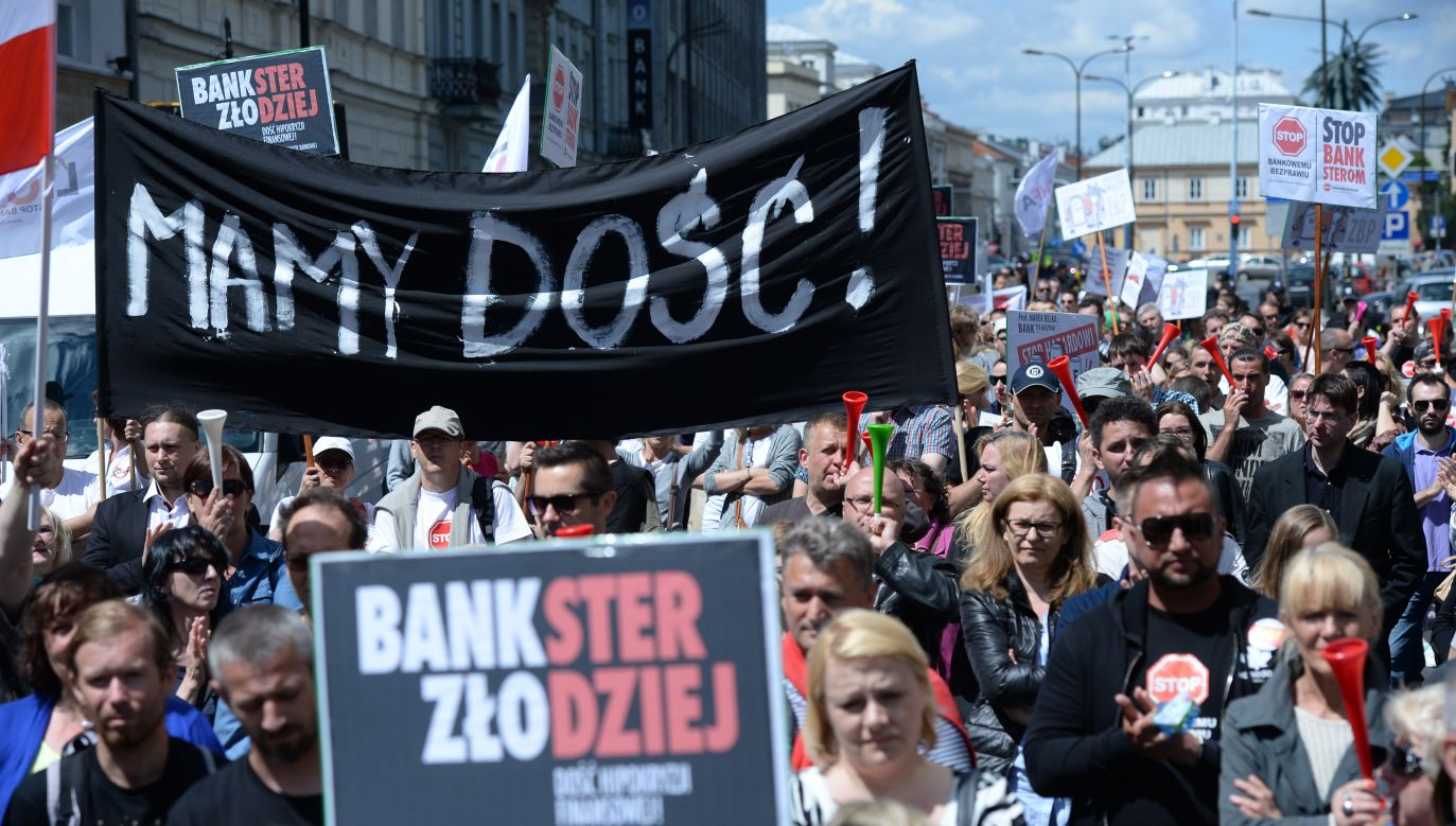 A scene from a protest organized by a group dedicated to the protection of Swiss Franc mortgage borrowers. One of the signs reads: