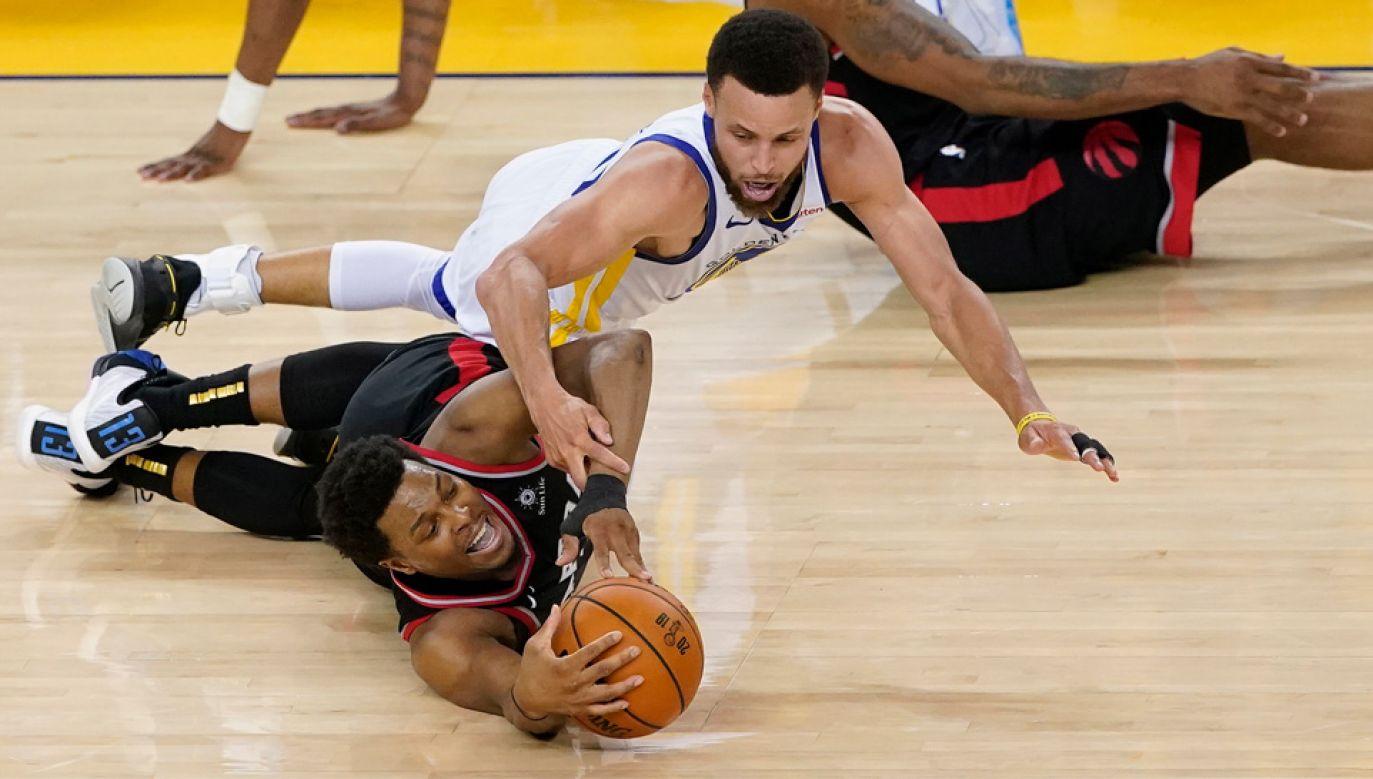 Raprtors Kyle'a Lowry'ego (czarna koszulka) prowadzą finale NBA z Warriors 2-1 (fot. PAP/EPA/JOHN G MABANGLO)