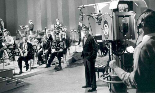 Leonard Bernstein z członkami nowojorskiej filharmonii w studiu telewizyjnym, około 1958 roku. Fot. Bert Bial - New York Philharmonic Archives, CC BY 2.5, https://commons.wikimedia.org/w/index.php?curid=8775008