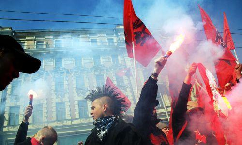 Członkowie lewicowej grupy Czerwona Młodzieżowa Awangarda podczas imprezy w Moskwie z okazji święta pracy. Krzyczą slogany i trzymają zapalone race. 1 maja 2006 r. Fot. Oleg Nikishin / Getty Images