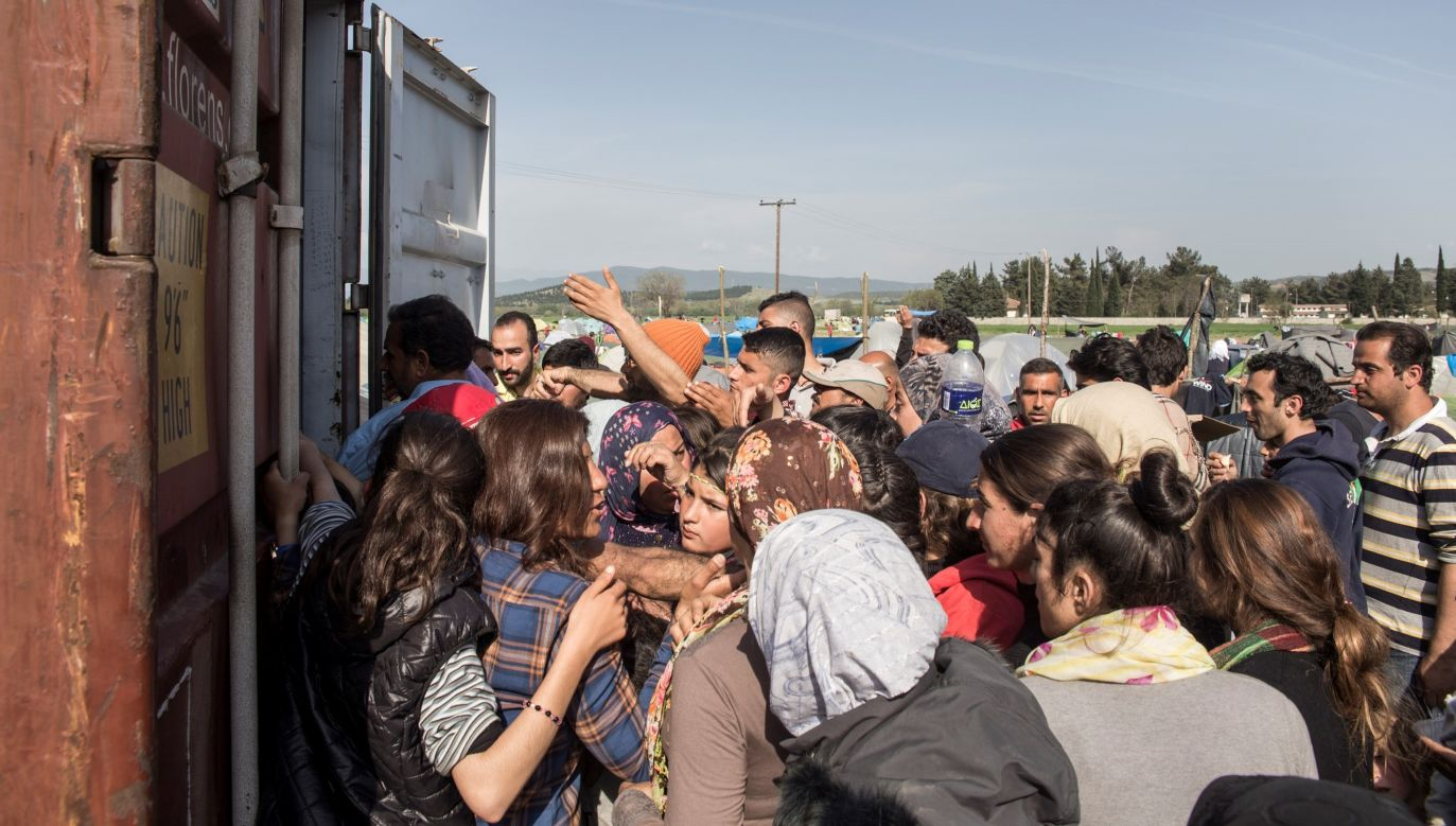 Refugees receive foods from volunteers at a refugee camp in Greece. Photo: RoberAstorgano/Anadolu Agency/Getty Images)
