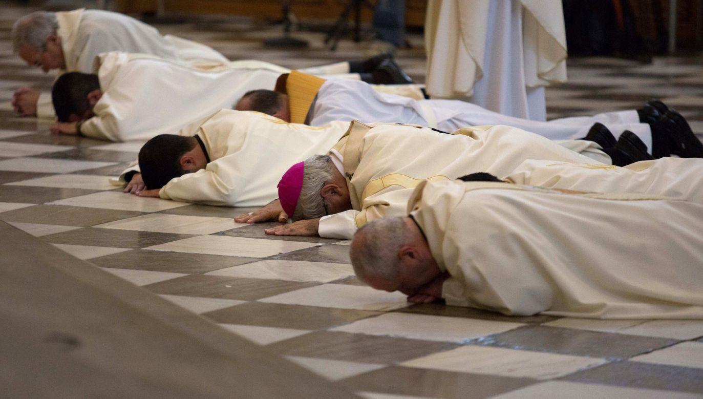 Arcybiskup Grenady Francisco Javier Martinez i księża z południowej Hiszpanii leżą  przed ołtarzem, prosząc o wybaczenie w związku z oskarżeniami o wykorzystywanie seksualne nieletnich przez duchownych tamtejszego Kościoła. Zdjęcie wykonano 23 listopada 2014 r. Fot. REUTERS / Pepe Marin