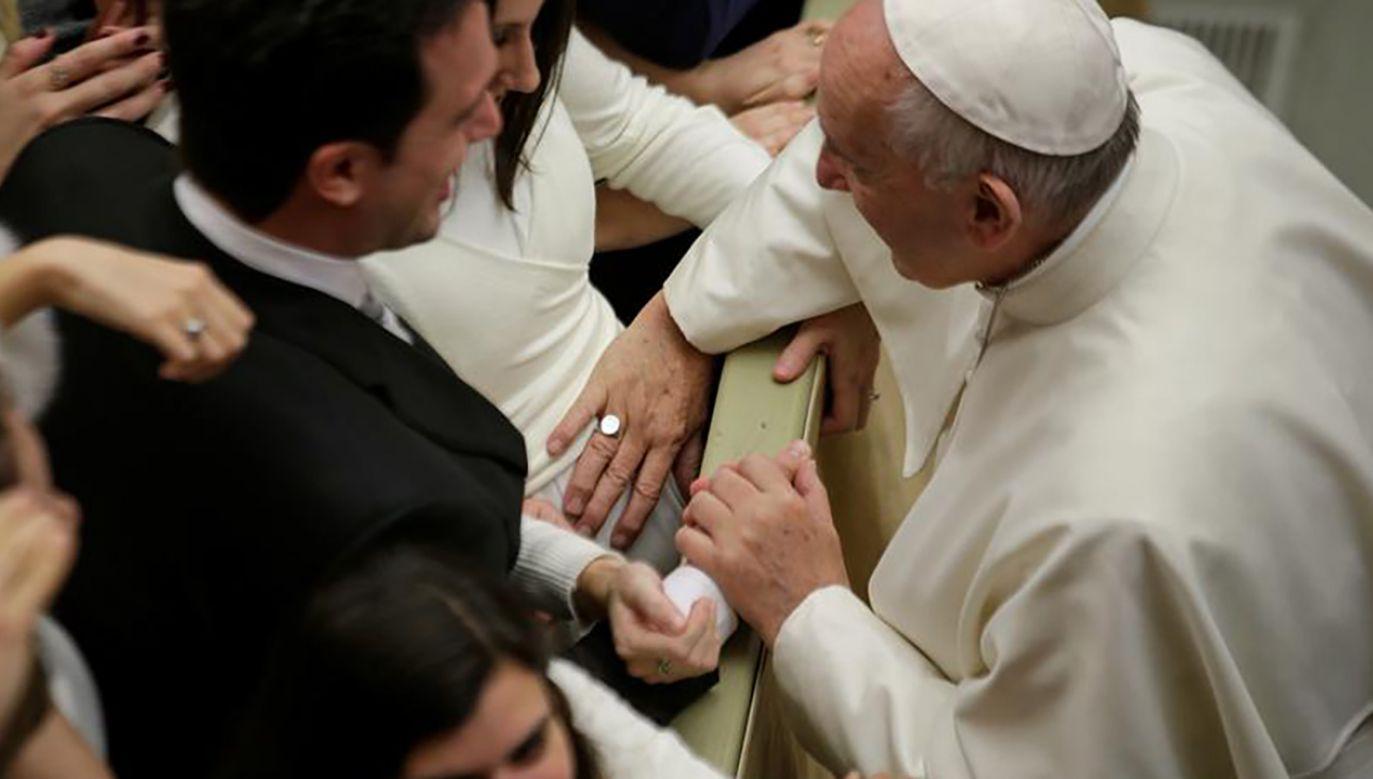 Papież Franciszek błogosławi ciężarną kobietę, dotykając jej brzucha podczas audiencji generalnej w Watykanie (fot. REUTERS/Max Rossi)