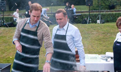 Wellington, Nowa Zelandia, 18 stycznia 2010 r. Książę William i John Key, premier Nowej Zelandii, przygotowują mięso na grillu w Premiere House podczas pierwszej wizyty Anglika – drugiego w kolejności następcy tronu Wielkiej Brytanii – w kraju na antypodach. Fot. Samir Hussein / WireImage