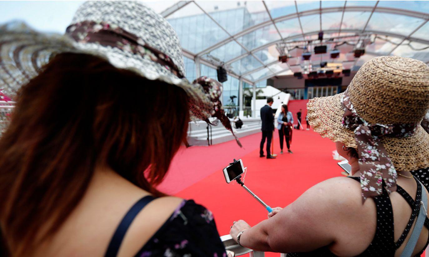 Ludzie robiący selfie przed czerwonym dywanem w Cannes (fot. PAP/EPA/IAN LANGSDON)