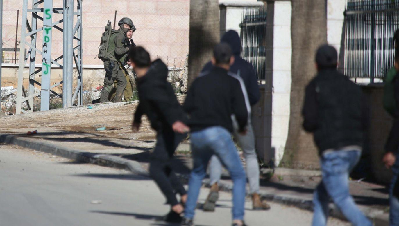 Palestyńczycy rzucają kamieniami w izraelskich żołnierzy w trakcie akcji na Zachodnim Brzegu (fot. Issam Rimawi/Anadolu Agency/Getty Images)