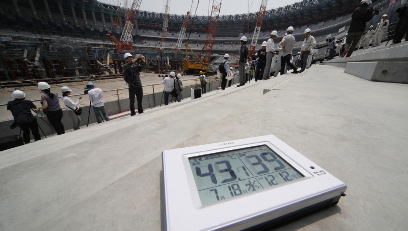 Termometr pokazuje temperaturę (L) i wilgotność na budowie stadionu na Igrzyska Olimpijskie w  Tokio w 2020 (fot.  PAP/EPA/KIMIMASA MAYAMA)