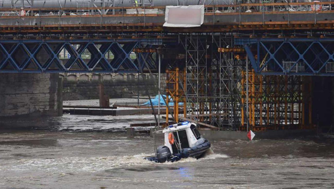 """""""Bosakami lub dziobem łodzi spychają konary do brzegu, gdzie wydobywają je wraz ze strażakami"""" (fot. malopolska.policja.gov.pl)"""