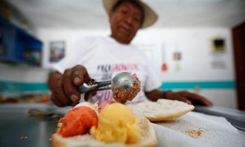 """Meksyk, 23 czerwca 2017 r. Simon Sanchez, 77-letni sprzedawca lodów w Xonacatlan na obrzeżach Mexico City, nakłada kulki lodów na kromkę chleba, by zrobić """"kanapkę z lodami"""" (powszechnie nazywaną tu Torta). Koszt 5-smakowej kanapki u Sancheza wynosi 0,77 dolarów. Fot. REUTERS/Edgard Garrido"""
