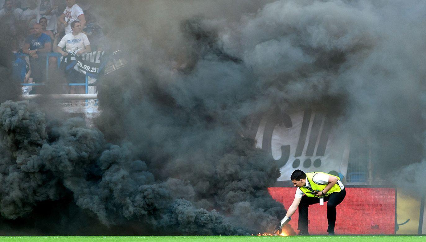 Kibice Lecha Poznań rzucający race dymne podczas meczu grupy mistrzowskiej ostatniej kolejki sezonu Ekstraklasy z Legią Warszawa (fot. PAP/Jakub Kaczmarczyk)