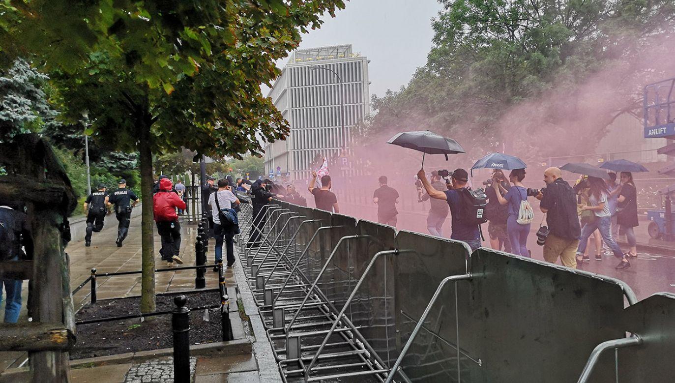 """Podczas protestów zostały odpalone flary i rozwinięto transparent o treści: """"Wypie…. Czas na sąd"""".(fot. Radosław Poszwiński)"""