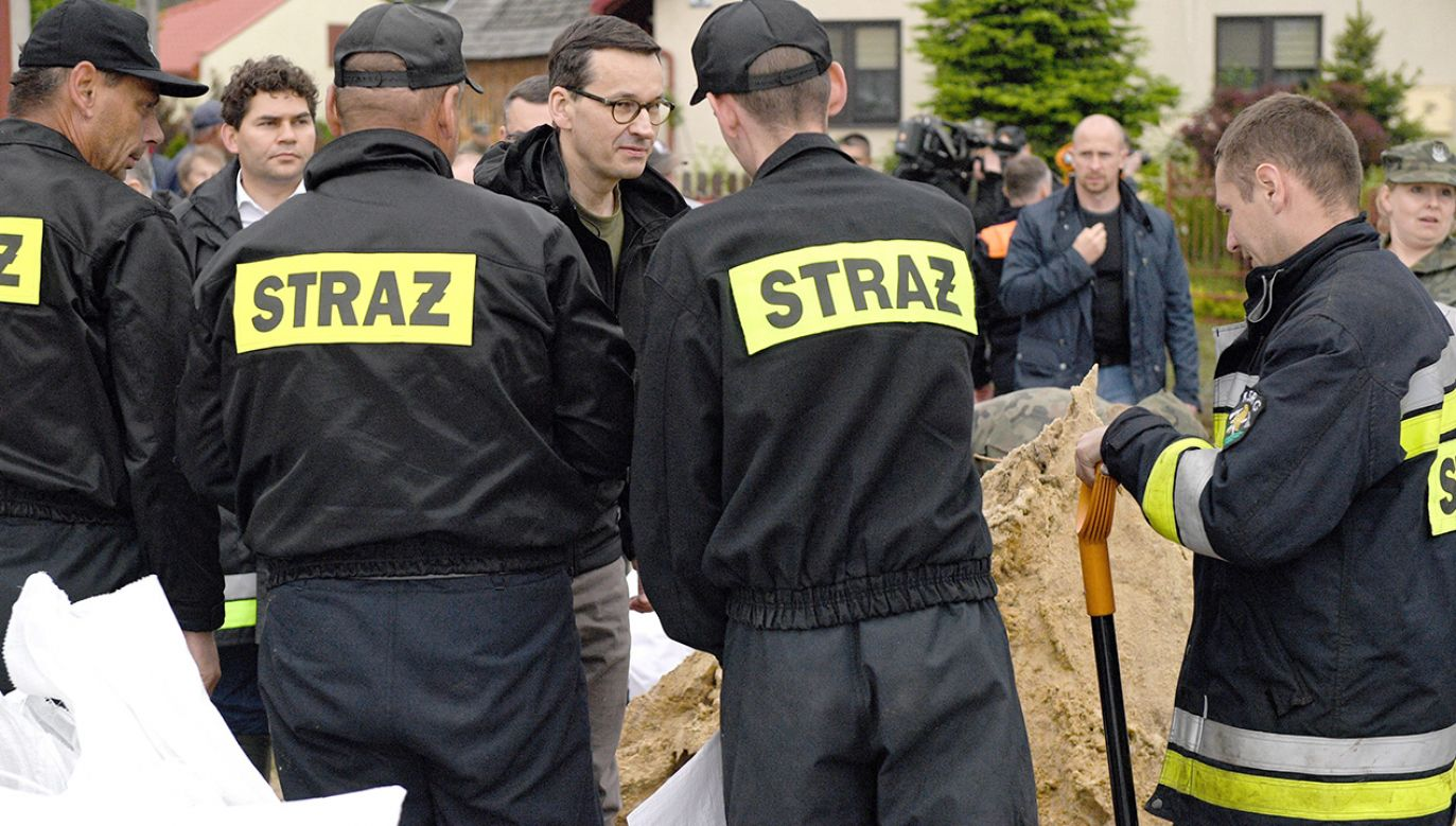 Premier Mateusz Morawiecki (C) w podtopionej przez wody Łęgu miejscowości Ruda (fot. PAP/Darek Delmanowicz)