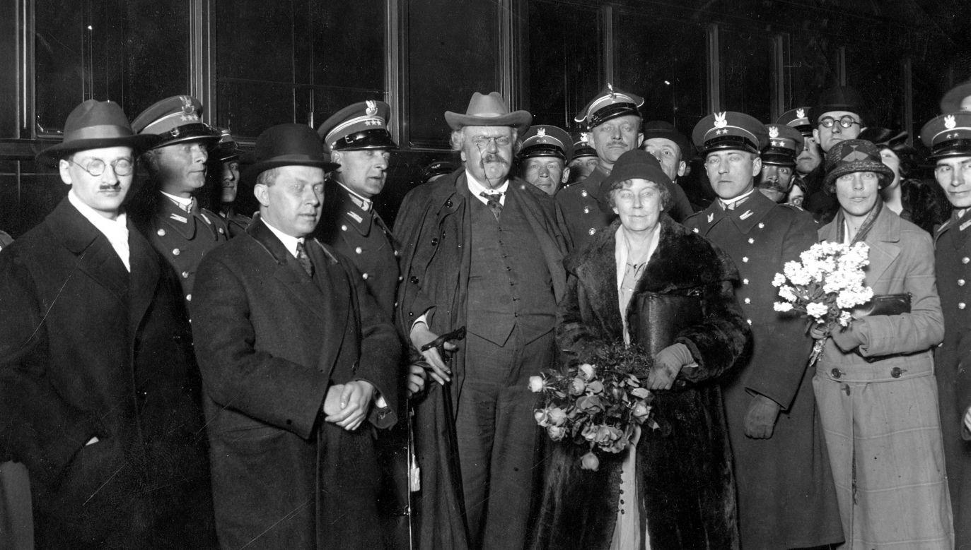 Wizyta Gilberta Keitha Chestertona (w środku, w kapeluszu) w kwietniu 1927 r. w Warszawie. Na dworcu witali go m.in. Wacław Borowy (1. z lewej), na prawo za nim rtm. Wacław Calewski, Ferdynand Goetel (2. z lewej) i za nim, też na prawo pułkownik Bolesław Wieniawa-Długoszowski. Na prawo od Chestertona major Adam Grocholski (z wąsami), adiutant ministra spraw wojskowych Józefa Piłsudskiego, a w głębi, w okularach Jan Lechoń. Fot. NAC/IKC, sygn. 1-K-2079-1
