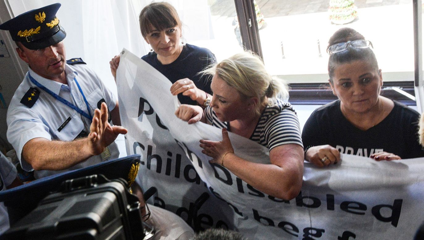 Protestujący w Sejmie rodzice dzieci niepełnosprawnych próbują wywiesić  baner (fot.  PAP/Jakub Kamiński)