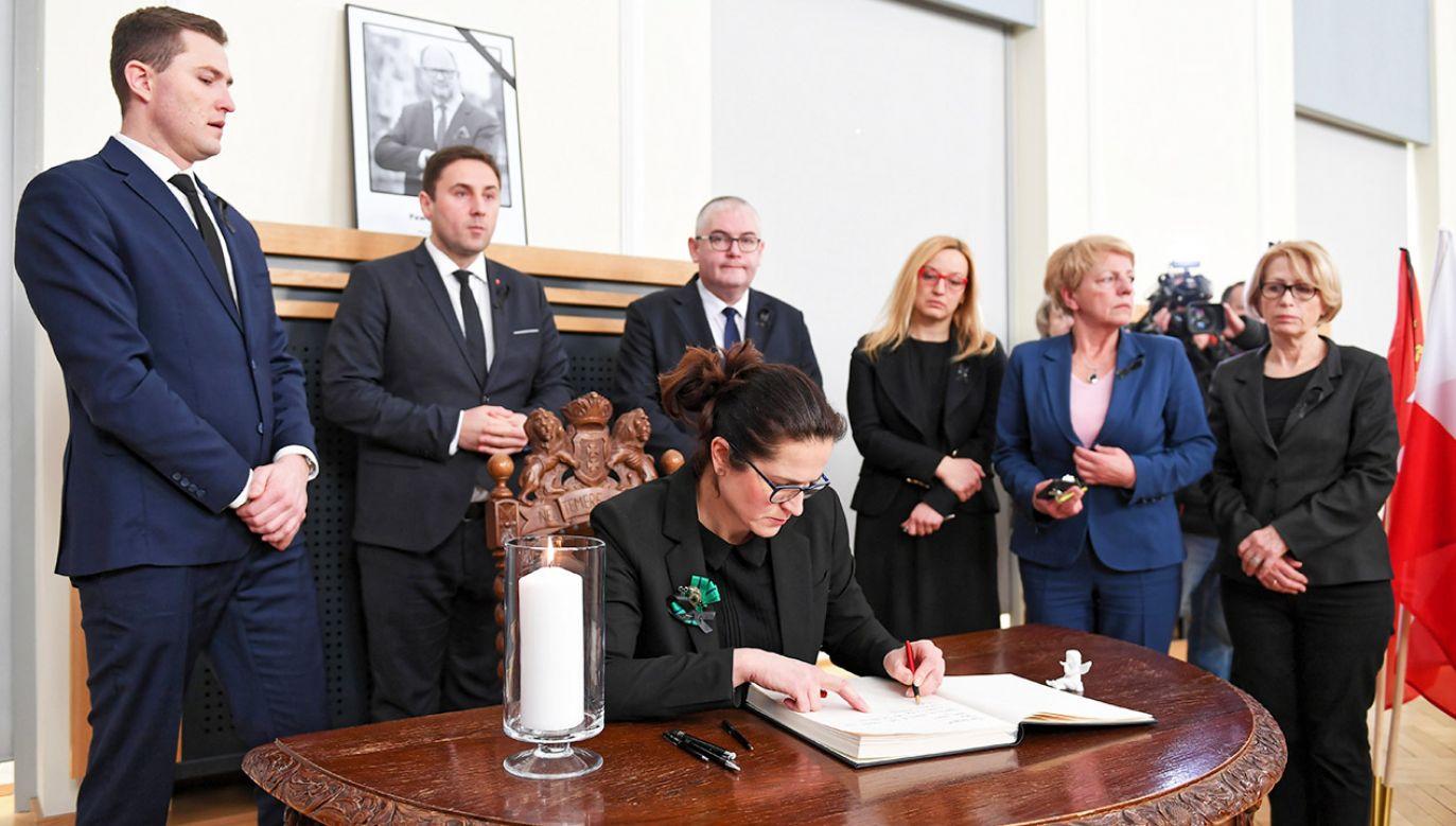 Wiceprezydent Gdańska wpisuje się do księgi pamiątkowej po zmarłym prezydencie (fot. PAP/Adam Warżawa)
