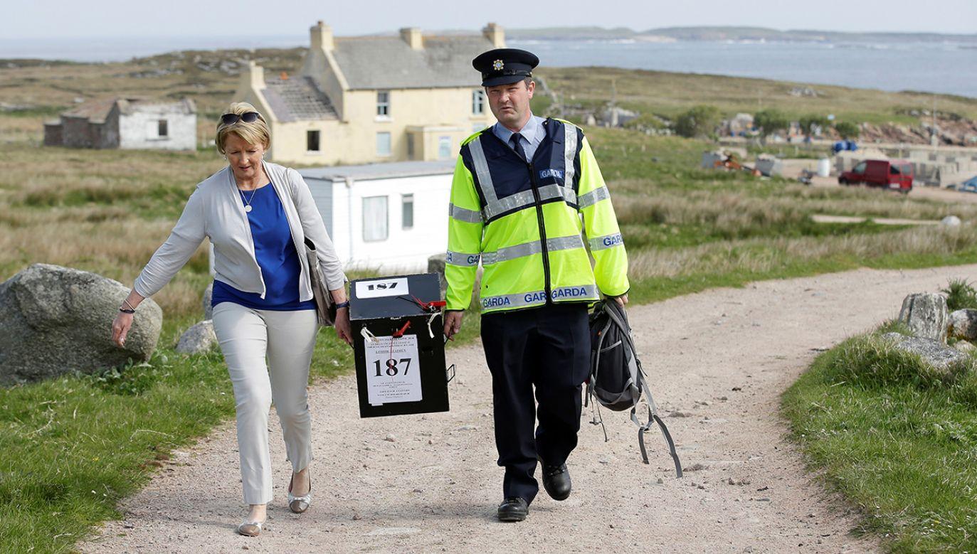 Policjant i urzędniczka Nancy Sharkey niosą urnę wyborczą w trakcie irlandzkiego referendum w sprawie liberalizacji prawa aborcyjnego na wyspie Gola w Irlandii (fot. REUTERS/Max Rossi)