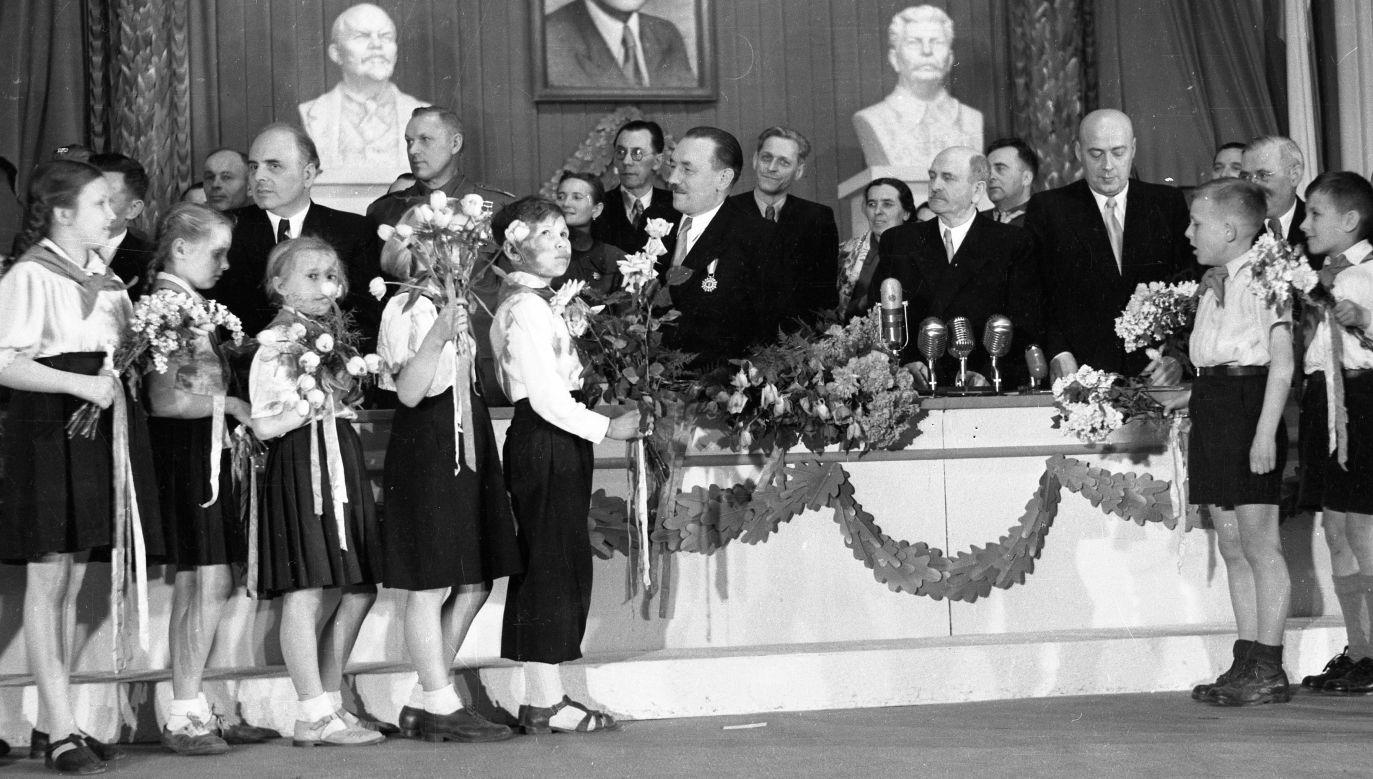 Dzieci składają życzenia Bolesławowi Bierutowi z okazji 60. urodzin. W uroczystości, którą zorganizowano w Teatrze Polskim w Warszawie 18 kwietnia 1952 roku, wzięli też udział: Jakub Berman (stoi w pierwszym rzędzie z lewej), marszałek Konstanty Rokossowski (drugi z lewej), Józef Cyrankiewicz (drugi z prawej) i Hilary Minc (z prawej zasłonięty). Fot. PAP/Wdowiński