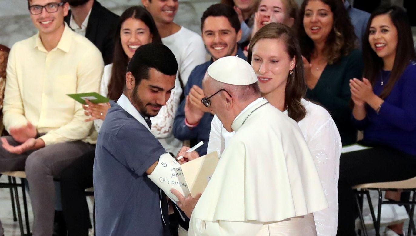 Papież Franciszek składa podpis na gipsie jednego ze świeckich uczestników synodu, 6 października 2018. Fot. REUTERS/Alessandro Bianchi