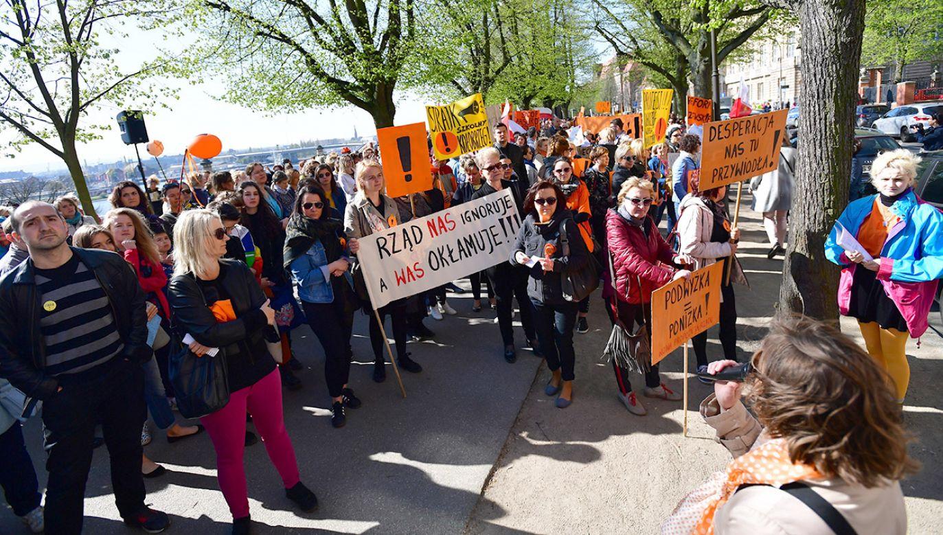 """Manifestujący przynieśli transparenty z hasłami: """"Podwyżka = poniżka"""", """"Desperacja nas tu przywiodła"""" (fot. PAP/Marcin Bielecki)"""