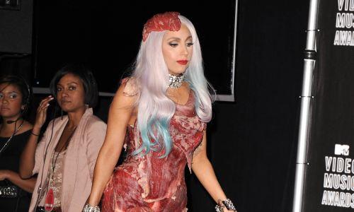 """Los Angeles, Kalifornia, wrzesień 2010 r.  Piosenkarz Lady Gaga na scenie 2010 MTV Video Music Awards odbiera nagrodę Wideo Roku. Maiał na sobie sukienkę i nakrycie głowy wykonane z surowej wołowiny. Ów """"mięsny strój"""", zaprojektowany przez Franca Fernandeza i stylizowany przez Nicolę Formichetti, został potępiony przez organizacje broniące praw zwierząt. Fot. Kevin Winter / Getty Images"""