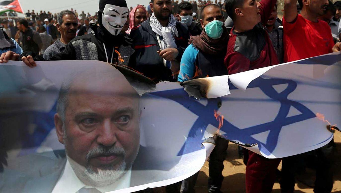 Palestyńscy demonstranci palą baner przedstawiający izraelską flagę i zdjęcie izraelskiego ministra obrony Avigdora Liebermana podczas protestu (fot. REUTERS/Ibraheem Abu Mustafa)