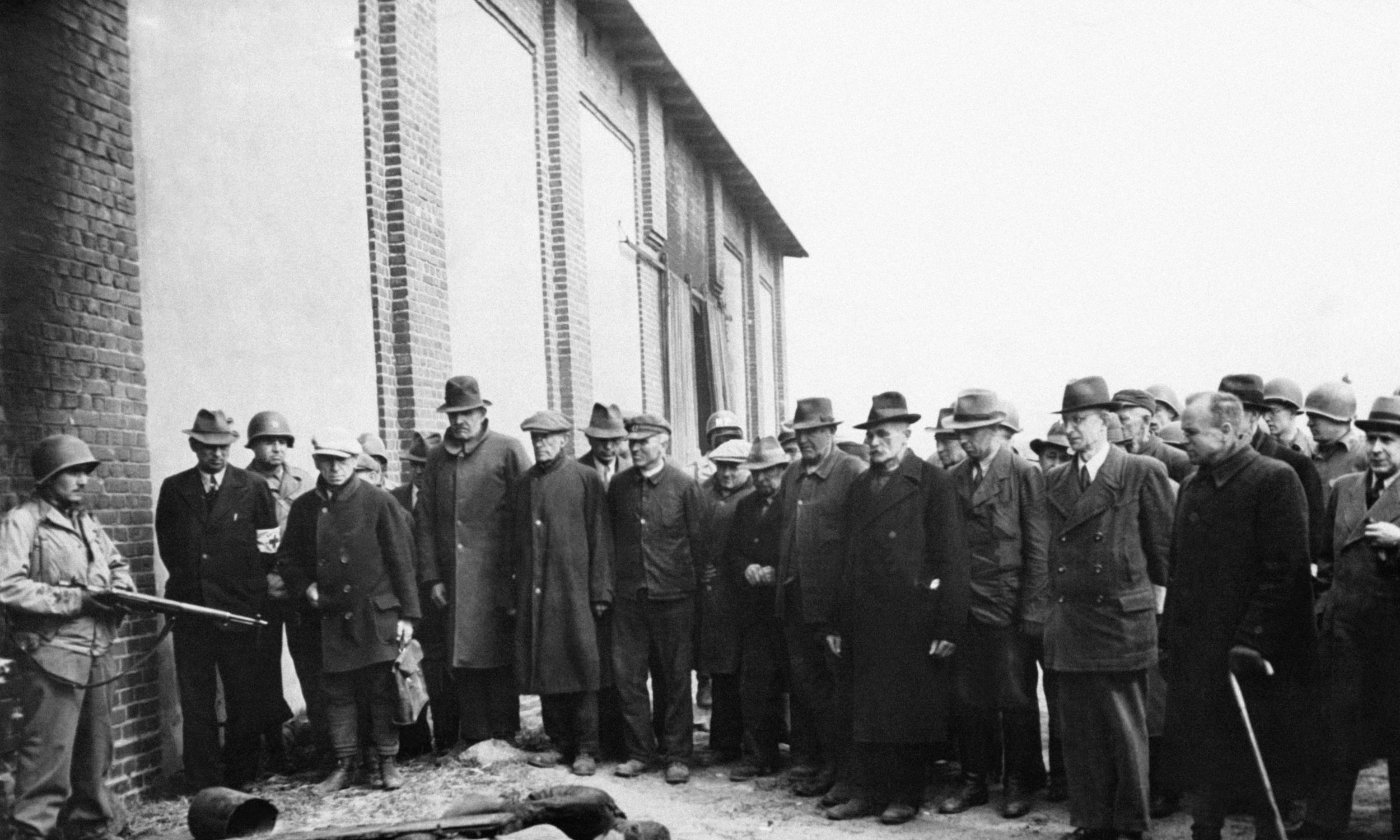 """Amerykański pułkownik George Lynch mówił do mieszkańców Gardelegen: """"Niektórzy powiedzą, że to dzieło nazistów. Inni wskażą na gestapo. Odpowiedzialność za to nie spoczywa jednak na żadnym na nich – odpowiedzialność ponoszą wszyscy Niemcy. Straciliście szacunek cywilizowanego świata"""". Na zdjęciu niemiecka ludność przyprowadzona przez Amerykanów do spalonej stodoły. Fot.  Keystone-France/Gamma-Rapho via Getty Images"""